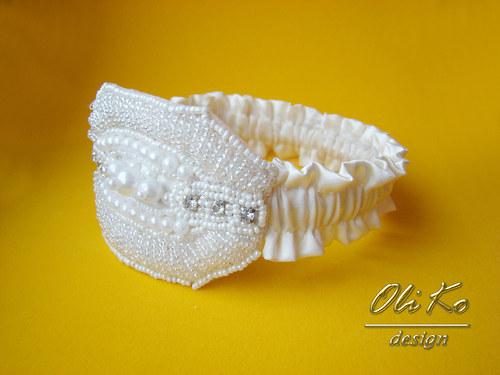 Ivory podvazek s koralkovou přezkou.