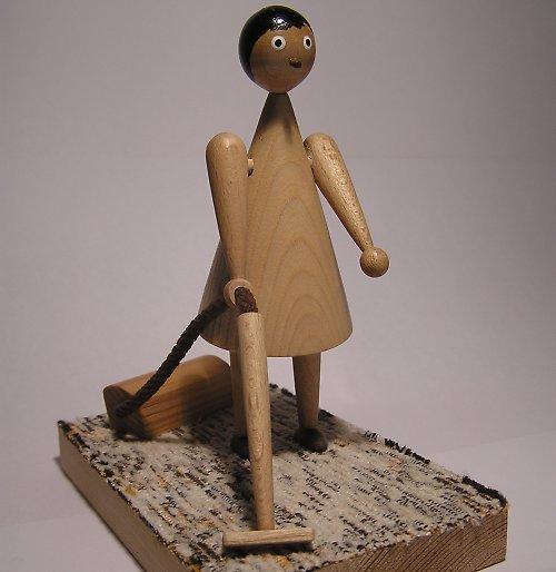 Dřevěná panenka s vysavačem na koberečku