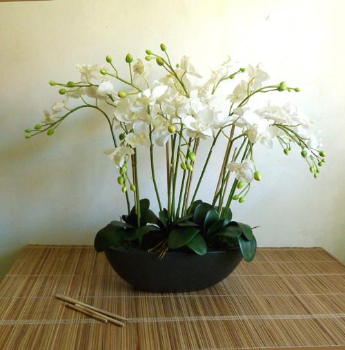 umělé bílé orchideje v oválné keramické černé míse